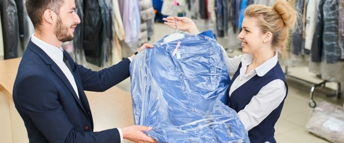 Man giving woman dry cleaning